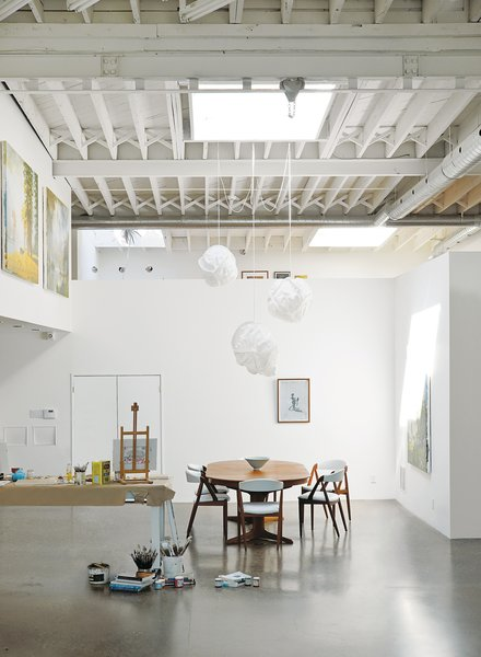 An airy haven was created in Toronto for artist Kent Monkman with the help of a painted white wood ceiling with exposed ductwork and original structural cross-bridging.