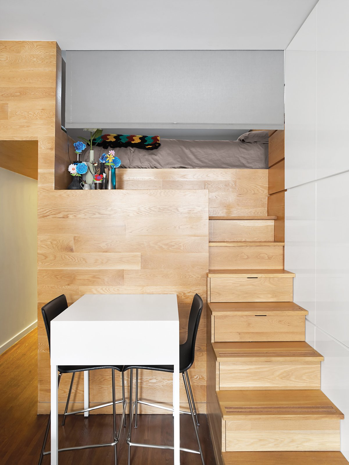 """Pozner credits Borowski with the idea to use a roller shade, purchased at the Shade Store, to close off the sleeping loft. The simple intervention, neither sound- nor lightproof, is sufficient to demarcate one """"room"""" from another. Tagged: Storage Room and Under Stairs Storage Type.  Photo 12 of 12 in The Manhattan Transformation"""
