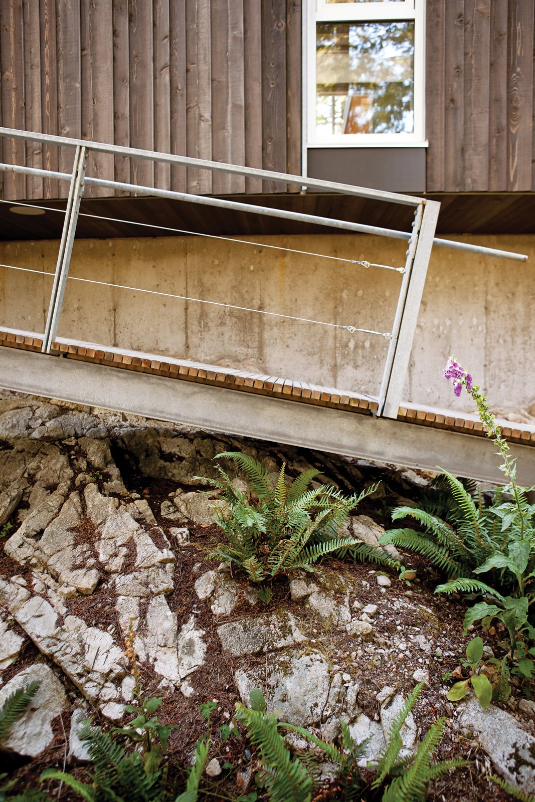 Outdoor, Flowers, Walkways, Shrubs, and Boulders Farther down on the site is a dock whose ramp is lowered by hand via weight-laden pulleys. The residence is accessible by private boat or water taxi only.  Photo 8 of 9 in When Living on the Edge is Super Comfortable
