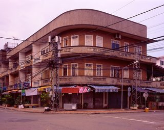 This building is in the old Chinese area of Vientiane, Ban Haysok, near the Mekong River and close to the old center of town. Probably built in the 1960's. At night this area is filled with street vendors selling noodles, Lao/Chinese desserts and other goodies. In the morning it is quiet and I felt the light on this particular morning really brought out the sensual lines of the building.