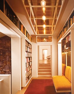 A hallway ends in a built-in bookshelf and a banquette backed with brass.