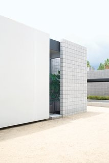 The exterior of the house consists of sandblasted masonry and Ferrari shade sails stretched on a steel frame.