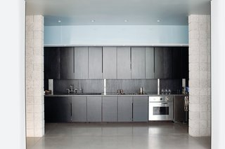 """""""Neither of us were too keen on the idea of having handles on the closets or cabinets,"""" says Atherton. So they cut narrow slots at the edge of the kitchen cabinet fronts to serve as hand pulls."""