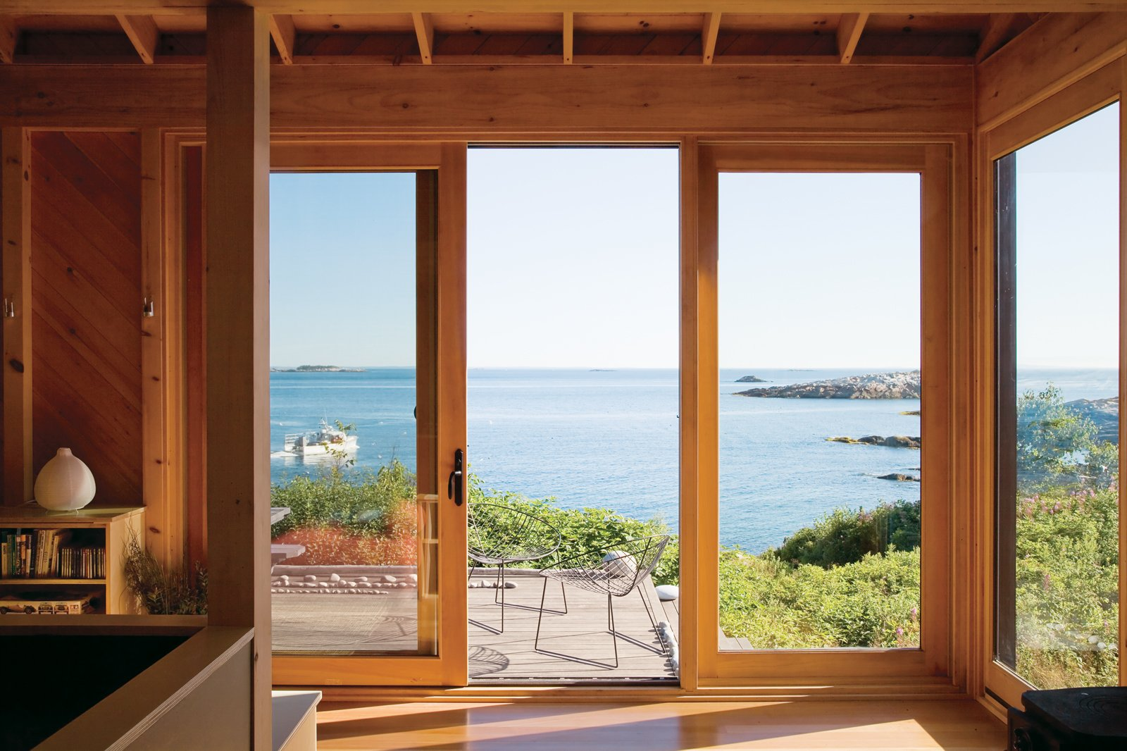 Outdoor and Small Patio, Porch, Deck The deck off the front is also minimally furnished with elegant lines of beach rock and two Leaf chairs by Arper.  Photo 6 of 21 in A Tiny Cabin is This Writer's Off the Grid Getaway