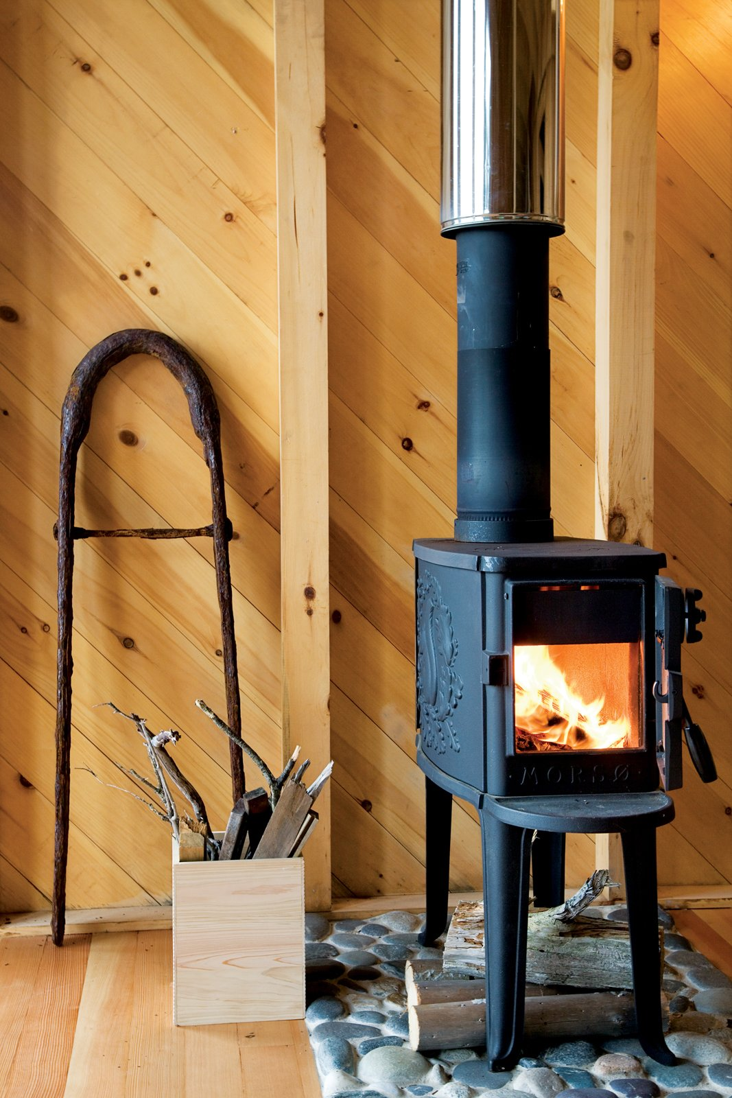 The diminutive Morsø wood stove and its hearth of local Criehaven beach stone gives off enough heat to warm the entire cottage.  Photo 7 of 21 in A Tiny Cabin is This Writer's Off the Grid Getaway