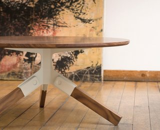 The Conrad coffee table has a solid walnut top and legs; each leg snaps into the stamped steel bracket without the use of hardware.