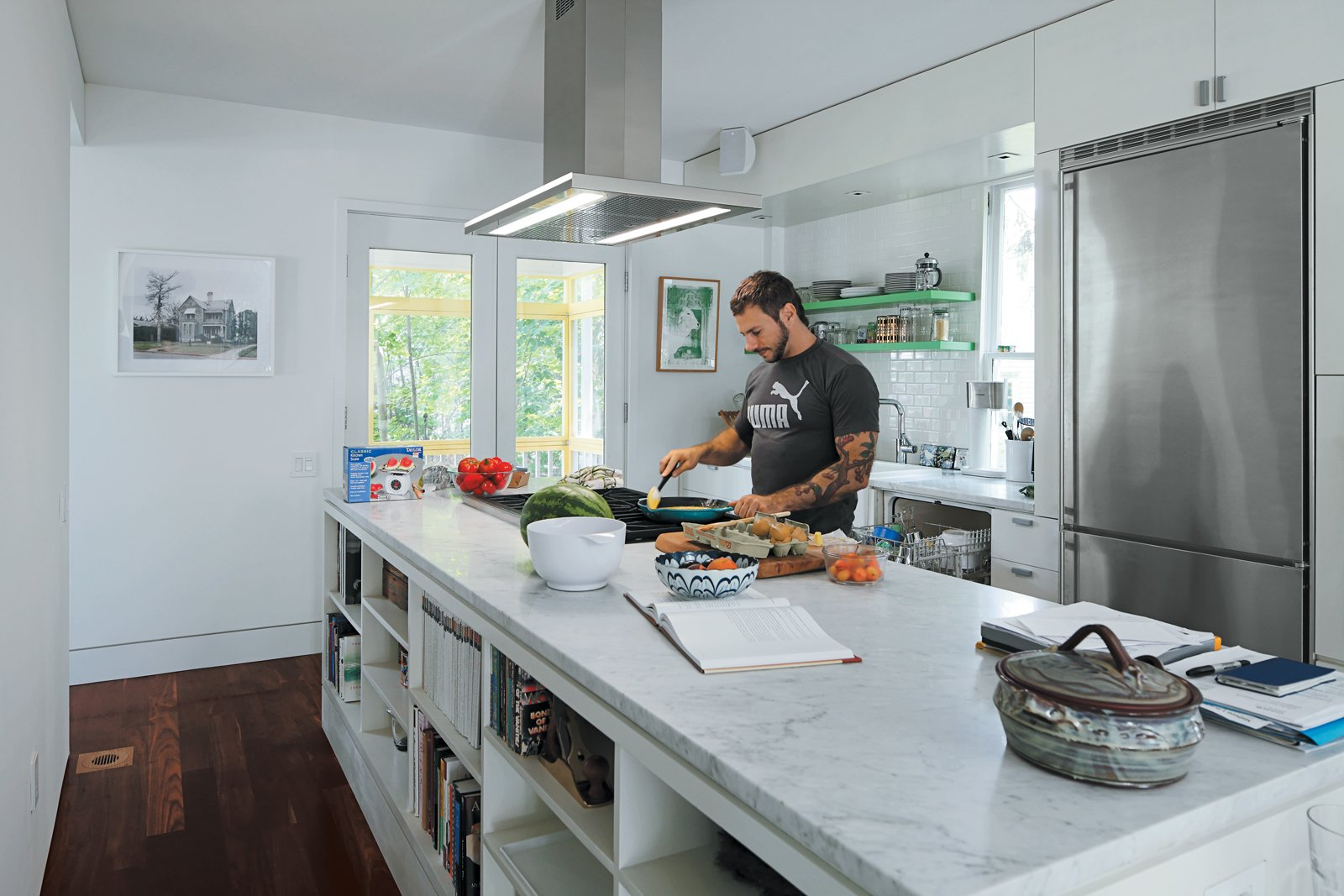 Kitchen, Marble Counter, Dark Hardwood Floor, Refrigerator, and Range To accommodate his passion for cooking, Renaldi insisted on the long Carrara marble countertop, a niche for cookware, and ultra-contemporary appliances.  Photo 6 of 11 in An 1850 schoolhouse in Milford, Pennsylvania