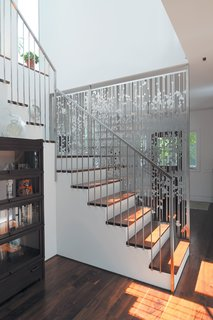 In a renovation of an existing farmhouse, a hanging screen composed of aluminum circles and lines, cut with a CNC water jet, separates the entry from the staircase and rear kitchen area.