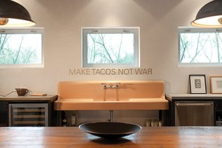In the kitchen, Make Tacos Not War, by San Antonio-based artist Alejandro Diaz, is mounted over a putty-colored sink Hill Salvaged from a demolition yard.