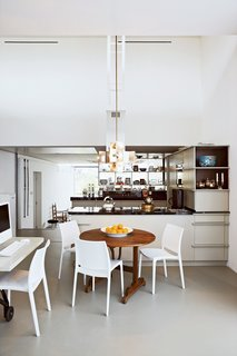 This Home Takes Recycling to the Next Level - Photo 3 of 13 - The kitchen frames a natural division between the public and private spaces of the house. The couple's private dining area features a round wooden table by Frank Bolink, and white chairs that are from Hema, a low-cost Dutch retailer.