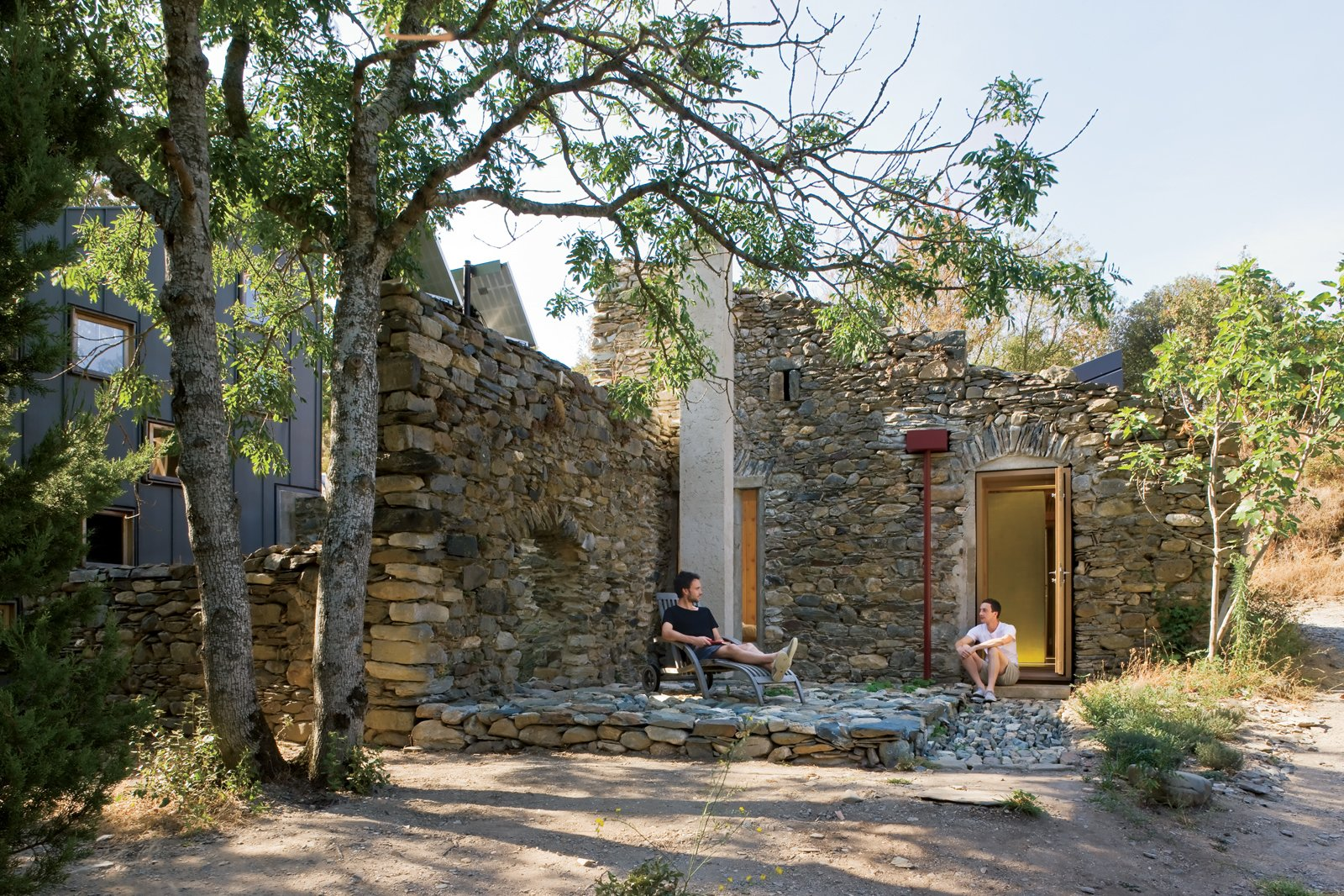 "Exterior, Stone Siding Material, and House Building Type ""We really wanted to capture the ruinous quality of this old building rather than do something overtly new,"" Blee says. Before construction could begin, however, he and Halligan had to patch the remaining walls using stones found in the nearby river. Wherever a wall had collapsed, the designers inserted framing to create windows and doors. For the roof, they turned to the original tiles. ""My father's terrible at throwing things away,"" Blee says. ""We took the tiles off 30 years ago, as it was too dangerous to have them up there. They've been sitting in the fields ever since, and this was out last chance to use them.""  Photo 6 of 6 in A Couple Restores a Seemingly Hopeless Mill in France"