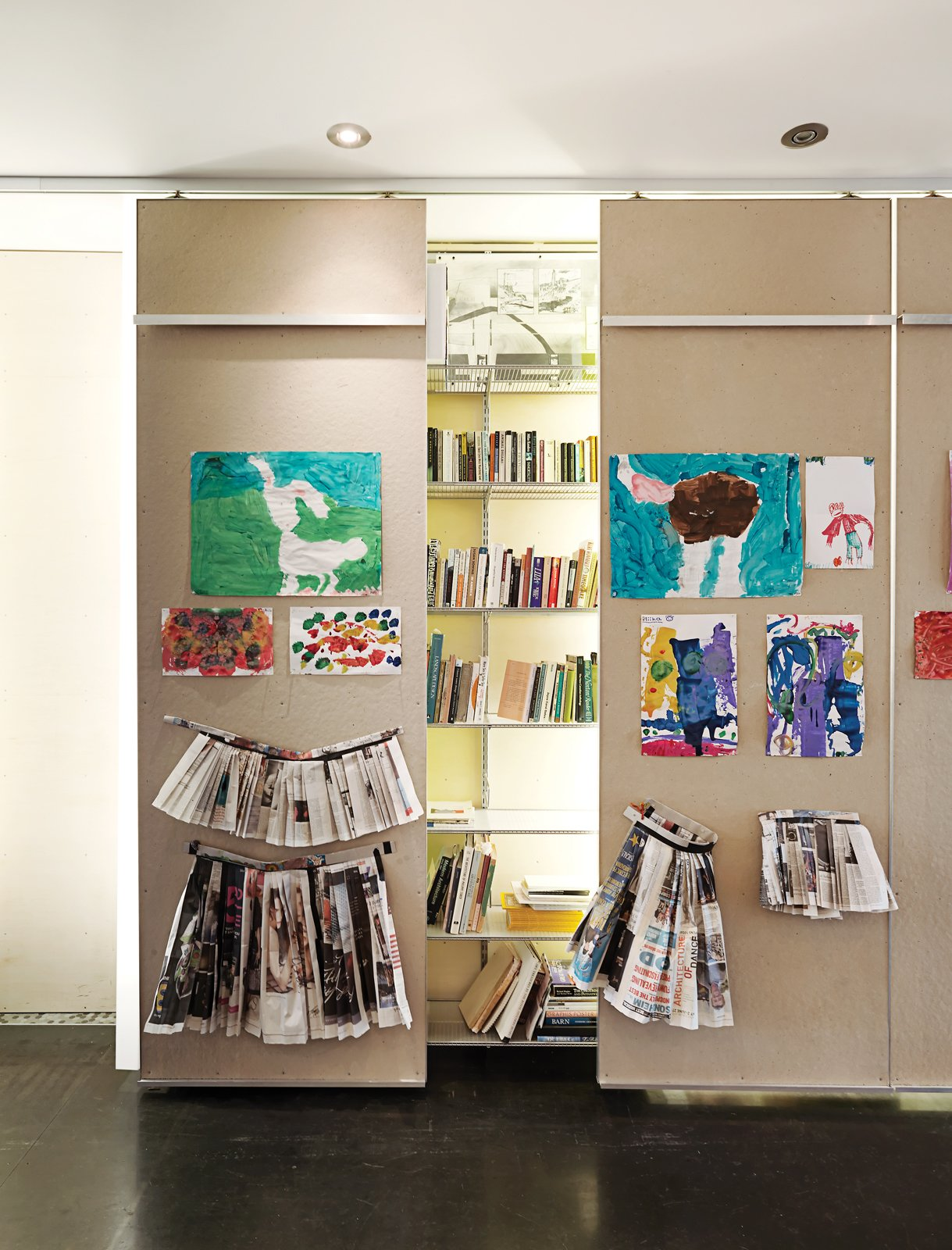 Storage Room, Closet Storage Type, and Shelves Storage Type In the ground-floor gallery, 40-foot-long library shelving is punctuated by floor-to-ceiling columns made from white acrylic panels that conceal low-cost fluorescent-tube lighting.  Photo 3 of 9 in Just Redo It