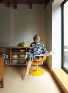 Lange reads the newspaper in a vintage Pierre Paulin Little Tulip chair for Artifort.