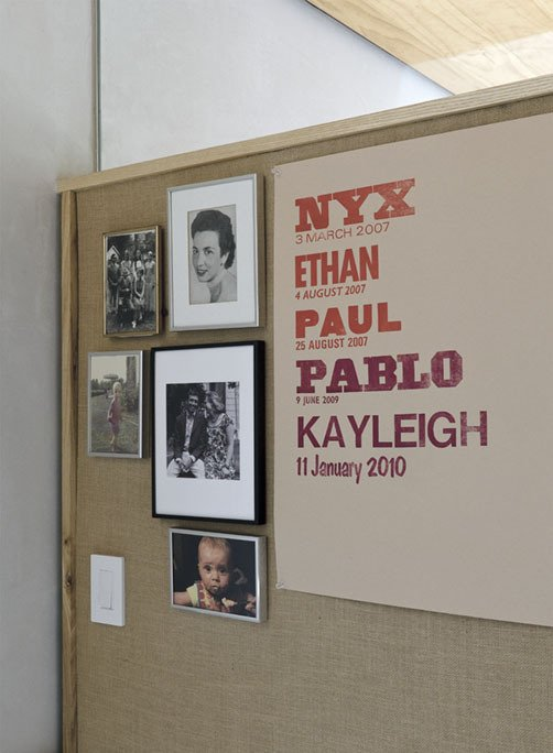Family pictures and a letterpress poster by Lange's mother, designer Martha Scotford, adorn a textile covered panel.  Photo 18 of 28 in Family Home Renovation in Brooklyn