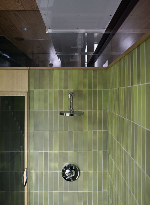 Green Heath tile, with their signature unevenness, provide a warm touch to the modern space. A cut-out in the glass allows the bather to dial in the right temperature on the Kohler fixture before stepping into the shower.  Photo 28 of 28 in Family Home Renovation in Brooklyn