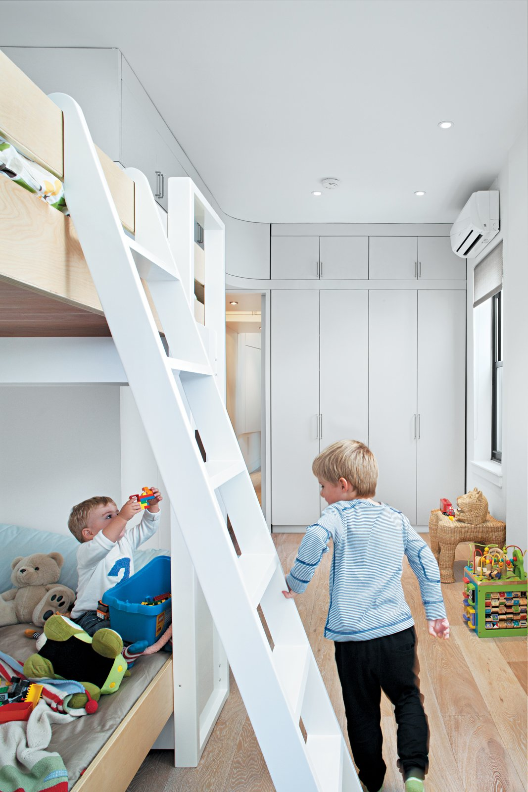 For now, Kimi, age six, and Darin, age two and a half, happily share a room and bunk bed. Kimi's clothes are stored on low shelves in the built-in closet, so he can dress himself, and the children's toys are stored within easy reach in open drawers.  Photo 5 of 8 in All Together Now