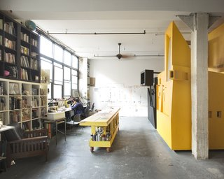 The five roommates share the common space in their high-ceiling loft. There's a large library and a studio. The large worktable gives Dreitlein and Ionescu, who together have a small art/architecture practice called The Objectionists, space to paint and make models.