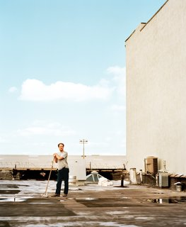 Cinematographer Wilmot Kidd sweeps the roof of the Red Hook industrial building that contains his home.