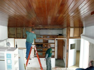 """One of the major changes to the house when it was rebuilt in 1950 was the raised height of the kitchen wall. """"Extending the wall up disguised the line of the butterfly ceiling,"""" says Altman. Here, a team of craftsmen commissioned by the RBF works on deconstructing the upper portion of a non-lode bearing wall separating the kitchen from the living room. Photo courtesy of the Rockefeller Brothers Fund."""