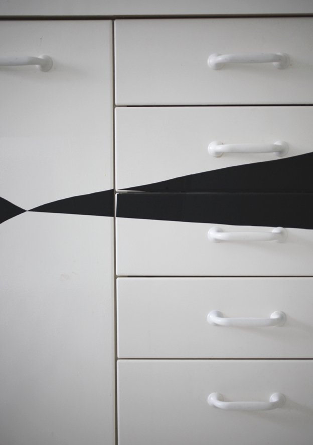 Since the couple knew they'd soon rip up the kitchen during a major pipe replacement and renovation, Susanna devised a cheap and easy way to prettify the nondescript cabinets in the meantime: she cut triangles out of black contact paper and affixed them to the cabinet fronts.  Photo 4 of 16 in Fine Finnish