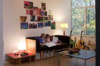 Back in the living room, the girls busy themselves with books. Hale designed and made the plywood couch with built-in book storage as well as the plywood-and-red-plastic-laminate side table. Hale's partner at Shed Architecture and Design, Thomas Schaer, created the Richlite-topped, steel-base coffee table.