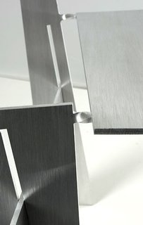 Each chair is folded from a sheet of 6-mm-thick aluminum. The points where the metal is twisted become delicate-looking hinges.