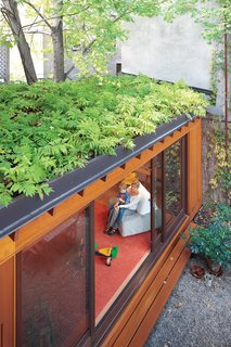 A small, single-story addition to the row house adds a playroom without eating up too much outdoor space. A green roof also helps makes up for lost garden beds, while creating attractive, leafy views from the second and third floors. In summer, when the sliding doors are left wide open, indoor and outdoor spaces blend together.