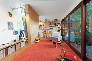 One wall section in the playroom juts in to sidestep a mature tree outside, while slender windows allow the kids to monitor its progress through the seasons.
