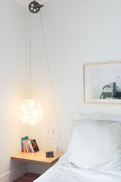 """For a simple, low-cost bedside reading light with a dash of industrial style, Bernier ran a standard-issue cord set through a vintage clothesline pulley, which he picked up at a flea market, on Thibault's side of the bed. """"If she ever wants it to be higher, she can easily adjust it,"""" he says."""