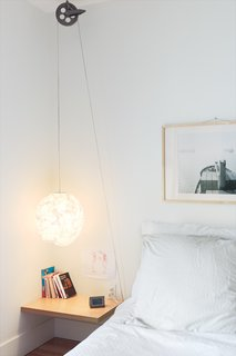 "Reel Simple<br><br>For a simple, low-cost bedside reading light with a dash of industrial style, Bernier ran a standard-issue cord set through a vintage clothesline pulley, which he picked up at a flea market, on Thibault's side of the bed. ""If she ever wants it to be higher, she can easily adjust it,"" he says."