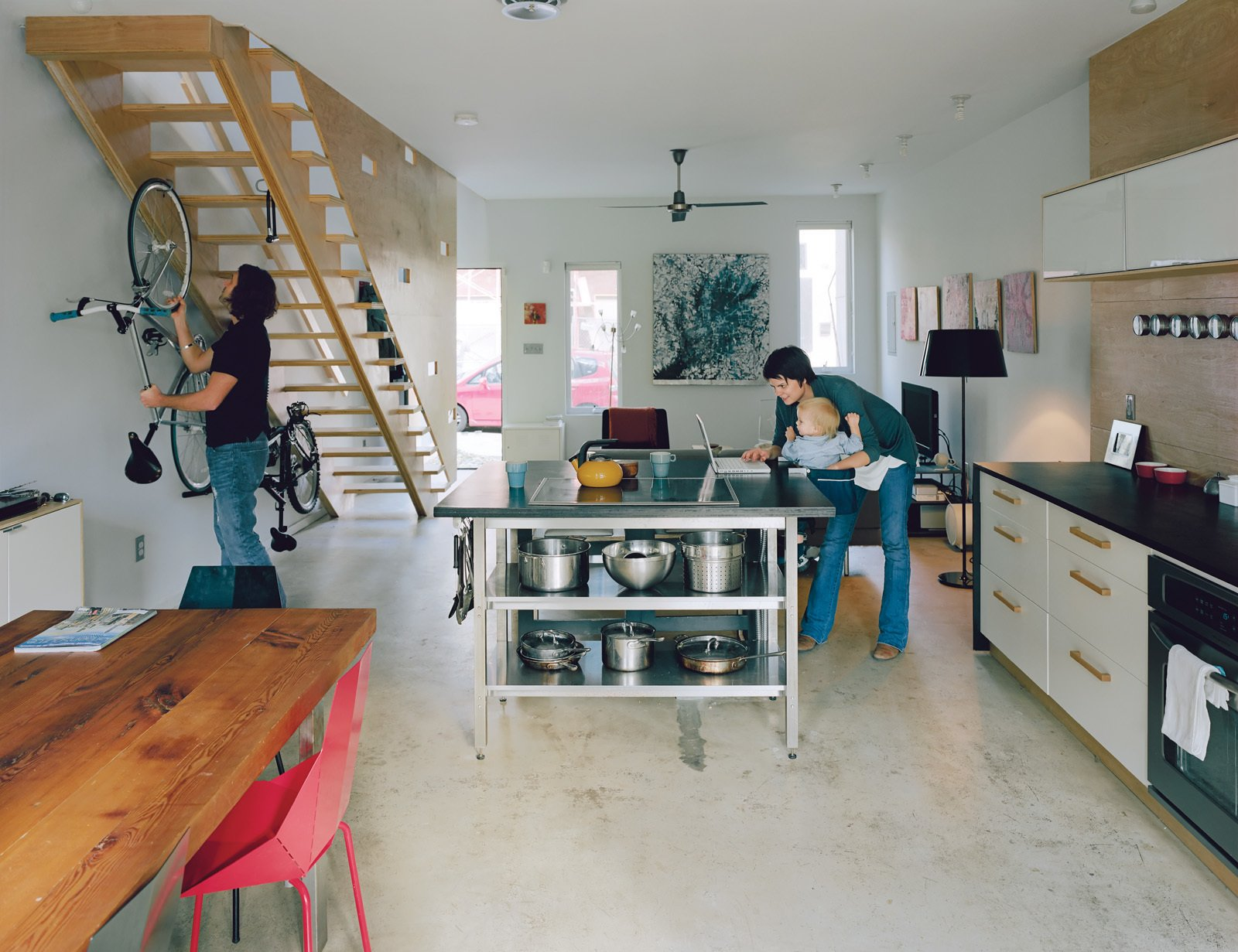 The long, rectangular bottom floor is one uninterrupted space. Bikes live beneath the stairs, and the kitchen island is a center of activity. The dining table was made by Bench Dog Design and the Real Good chairs are by Blu Dot. An inexpensive fan by Emerson and exposed CFLs are smart, low-cost options for the ceiling.  Photo 1 of 11 in Green Urban Housing in Philadelphia