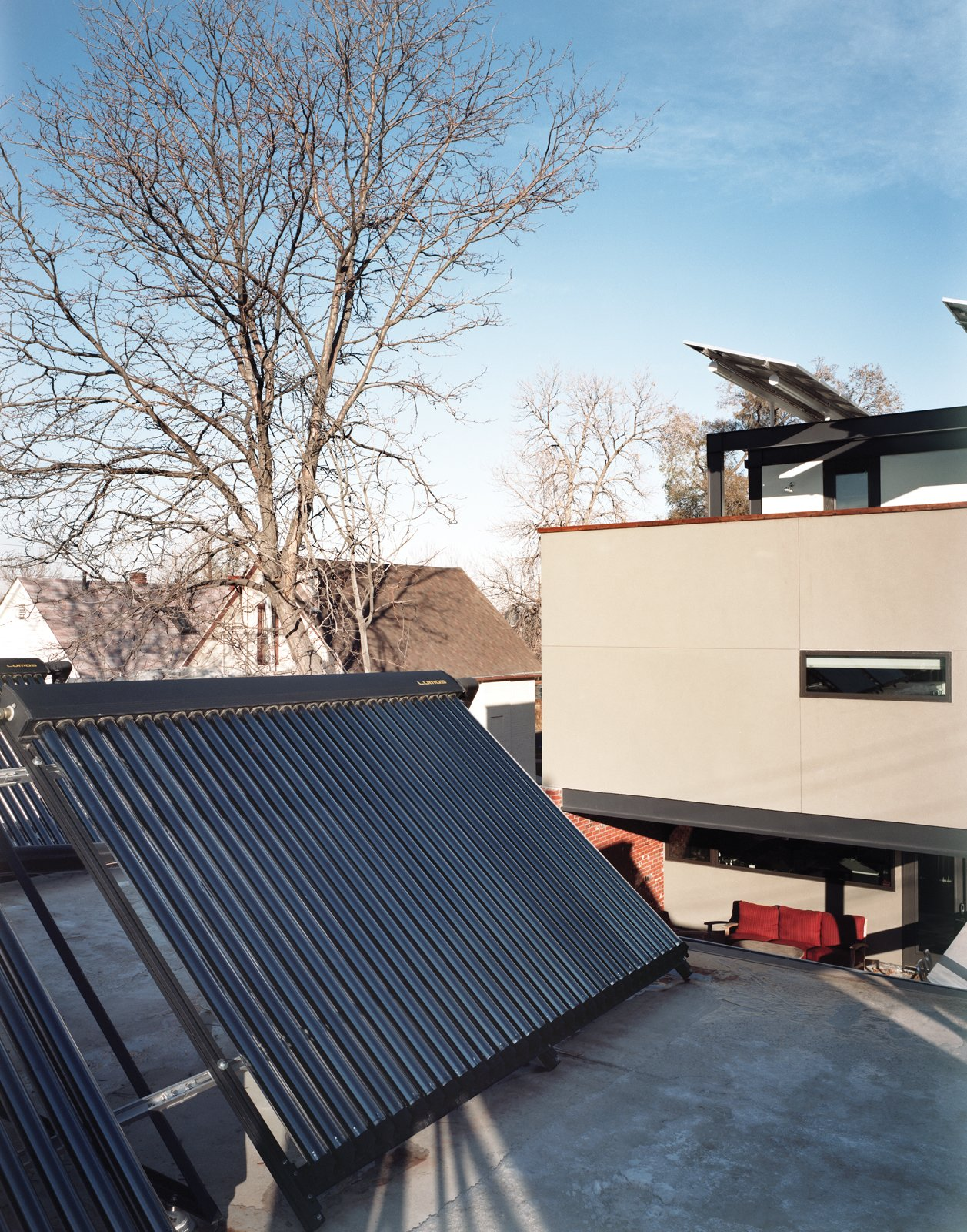 "An array of solar thermal tubes crowns the garage, and photovoltaic panels extend like wings over the third-floor deck. ""If we were going to make a big architectural move, we had to have reasons,"" Moore explains, referring to the conspicuous placement of the panels.  Photo 2 of 8 in Denver's Energy Efficient  Home"