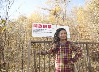 A Platform for Living - Photo 25 of 28 - The dreadlocked Ishii Hideaki grins at the gate to the Kobayashi's property.