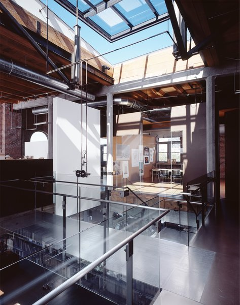 """Located in the historic Washington Shoe Building in the Pioneer Square Historic District, the office design limits its impact on the preexisting space. The open plan layout is pulled away from the perimeter walls to limit contact with the existing historic structure and to take advantage of better natural daylight, circulation paths through the office, and to avoid the favoritism associated with the """"corner office."""" Sustainable ideas were explored through the natural ventilation strategy (skylight and open stair for a chimney effect), not painting the warehouse walls or even the old windows (left """"as is""""), using masonite for floors and walls (a highly recycled content material left unpainted), and unpainted steel. Photo by Benjamin Benschneider."""