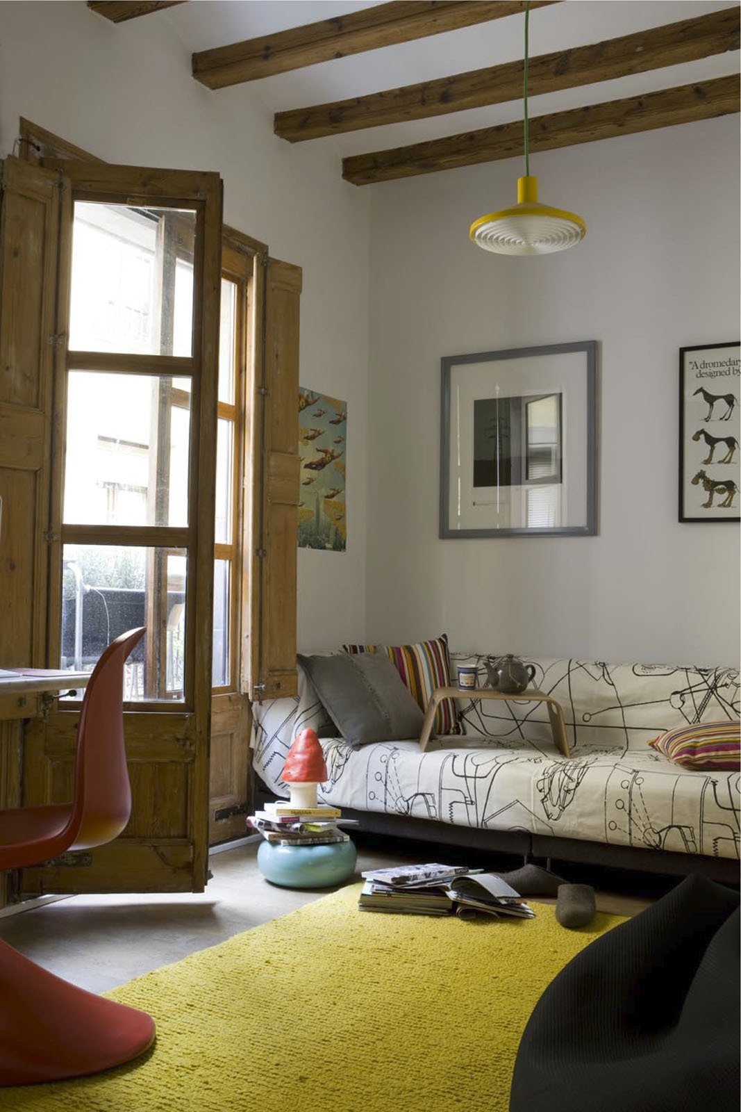 Wishing to avoid using harsh chemicals, the couple had the 18th-century beams and French doors in the living room and elsewhere sandblasted to rid them of woodlice. The rug, by Nani Marquina, is renewable and biodegradable as well as ethically produced.  Photo 9 of 10 in 10 Modern Renovations to Homes in Spain