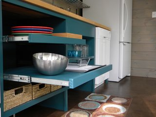 Made for easy reaching, these open pull-out shelves are in an ADA-compliant kitchen in a guesthouse designed by architecture firm Best & Associates. Although the shelves were designed without doors, they were painted inside and out with a turquoise paint for a uniform, finished look, and the sliding shelves mean that every inch can be accessed, even the very back of the shelves.