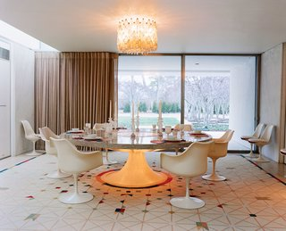 This dining room is centered around a custom Eero Saarinen-designed, marble-and-terrazzo table that's surrounded by Tulip chairs. A Venini chandelier hangs overhead.