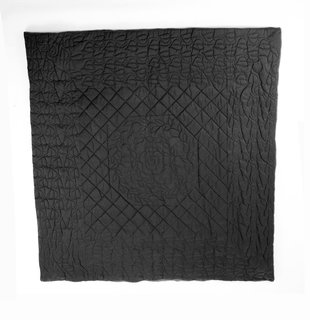 Wong's works grappled with perceptions of safety and security in post-9/11 America. This quilt is made from ballistic nylon, a material typically used in military applications as a protective shield from flying debris. Here, Wong uses the material in a quilt (a comforting object) with a rather traditional pattern, commenting on a need for a different sense of comfort and security.<br><br>Tobias Wong, <br><br>Bulletproof Quilted Duvet, 2004, ballistic nylon, cotton, and cotton flannel; Collection SFMOMA, gift of Josee Lepage; © Estate of Tobias Wong; photo: courtesy SFMOMA.