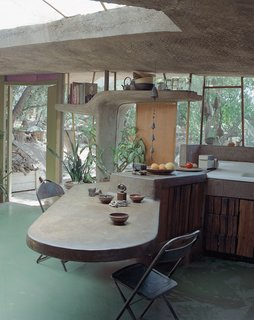 At a smaller scale than an entire building, a concrete, cantilevered countertop and table extends both inside and outside at the Arizona home of Italian architect Paolo Soleri. A sculptural shelf frames the window and door beyond, with rounded edges for a soft, supple feel.