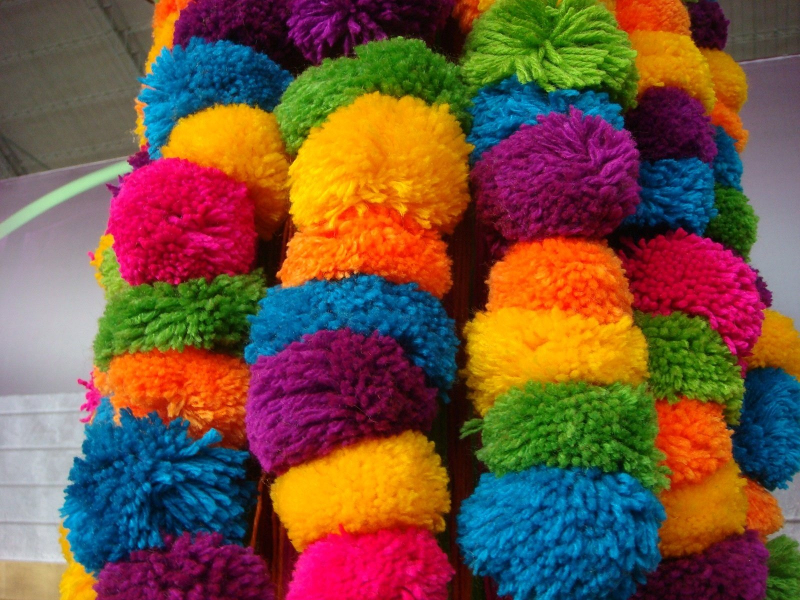 Colorful pompoms in all the vibrant colors found throughout the fair.  Photo 16 of 32 in Color Me Mad! from Peru Gift Show 2011
