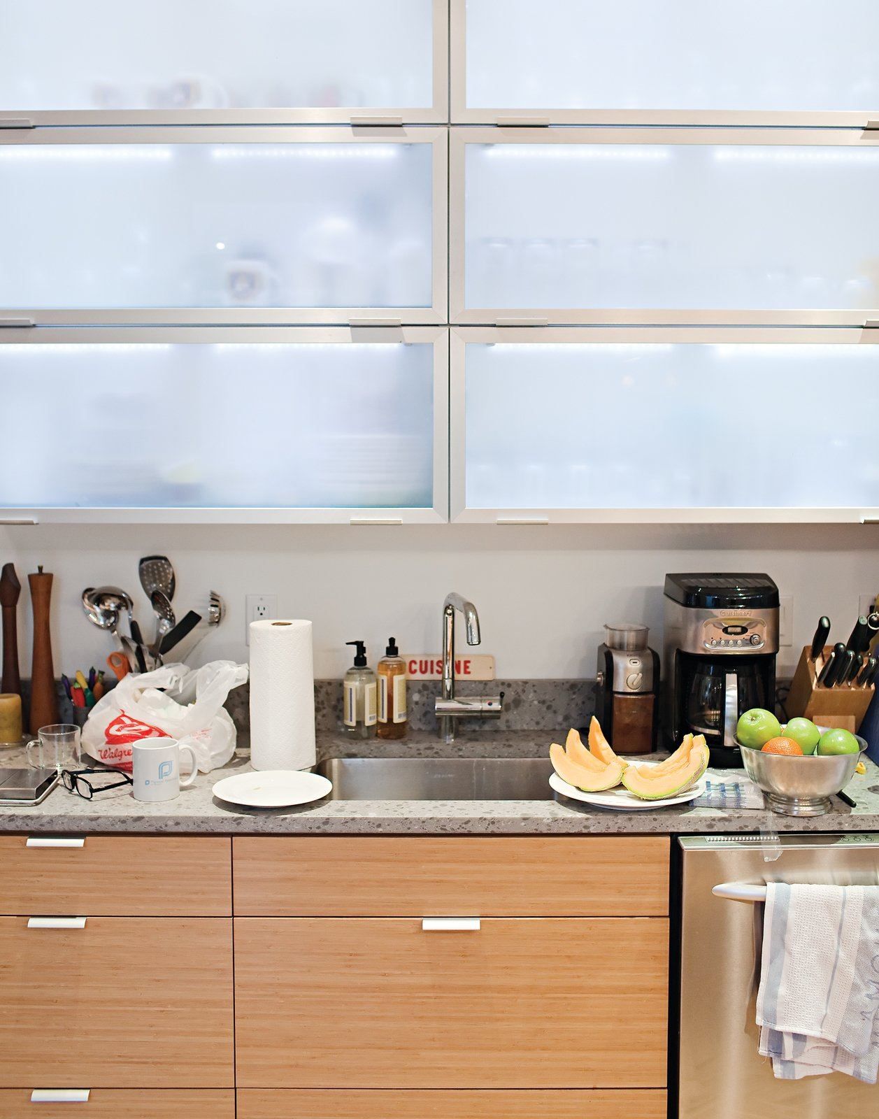 Frosted Tip  Church wanted open shelving above the kitchen counters, but DeSalvo convinced her to go with Ikea cabinets with frosted-glass doors to ensure a uniform look. He installed inexpensive strip LED lights by Zilotek on the top inside edge of the cabinets to provide ambient illumination and silhouette the contents inside.  Photo 9 of 25 in Come Sail Away