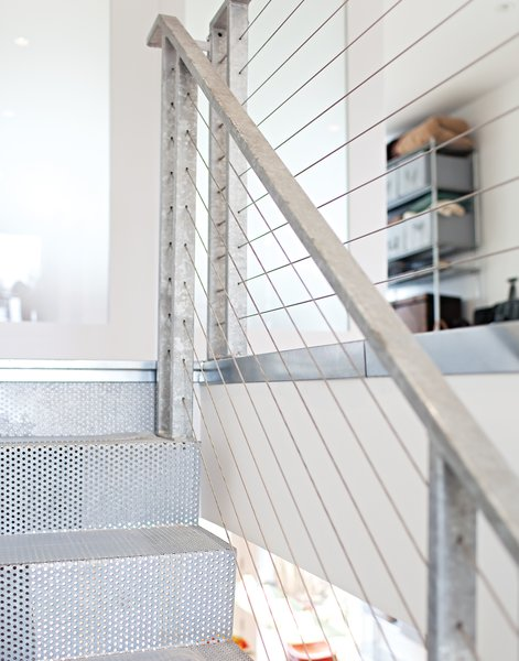 A mixture of perforated, bent-steel plates, tension cables, and galvanized-steel handrails and posts form a modern staircase that feels light and airy, despite its industrial materials. The perforations in the steel steps and the thinness of the tension cables keep the stair feeling open and transparent. Designed by architect John DeSalvo, it was inspired by a high-end staircase by French architect Jean Nouvel.