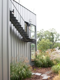 The second Jean Nouvel-inspired staircase lives outside, clinging to the side of the house and leading up to the roof deck, where there's a hot tub shaded by sun sails.