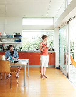 The bach was designed with a combined open-plan kitchen, living room, and dining area, for which Gerald designed a dining table that seats ten. Bare bulbs, open shelves, and bright orange MDF cabinets in the kitchen maintain the low-key vibe.