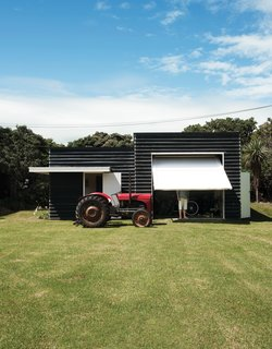 To accompany and complement his family's main house, architect Gerald Parsonson designed this easy, informal shed that adequately addresses the beachy life of the family. The site includes a boat shed and a tractor the family uses to pull their boat to and from the ramp.