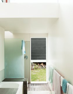 A bathroom with corrugated steel walls opens directly to the outdoors, making it easy to shower post-beach.