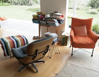 There are plenty of places to sprawl in the living room, including an Eames lounger and a custom-made orange chair.