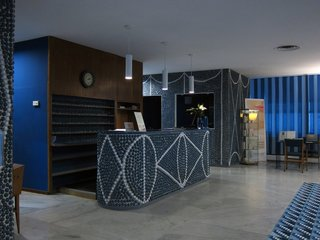 "The lobby gives visitors an immediate sense of the hotel's design vocabulary. With the exception of some wood accents, almost every surface is either blue or white. Thousands of ceramic ""pebbles"" are set into the walls, adding an almost unbelievable level of workmanship and craft to the interior."