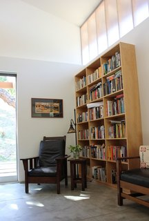 """Current owners melded their former dwelling's period furnishings—an L. & J.G. Stickley settee at right, William Morris attributed chair, and Handel lamp—with their new setting.  The reading area is """"an homage to our craftsman home we left to live here,"""" says owner Allison Morgan.  Hanging above, a work by Georgia-based artist Kathleen West, known for her contemporary take on Arts and Craft style block print, links past with present. [Photo Credit: Jodie Bass]"""