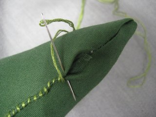 When he feels the right fluffiness, stitch the opening up with the green embroidery thread.